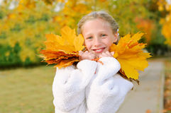 Girl with yellow leaves smiling Stock Images