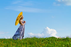 Girl with yellow parasol on meadow,. Girl with yellow standing sideways to camera, meadow in spring. Copy space royalty free stock photos