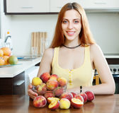Girl in yellow with peaches at home Stock Image