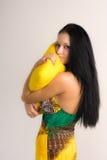 Girl with a yellow pillow Stock Photos