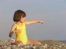 A girl in yellow plays on the beach at water Stock Photos