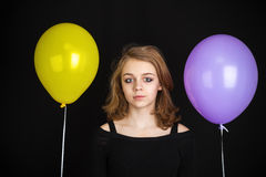 Girl with yellow and purple balloons over black Royalty Free Stock Photography