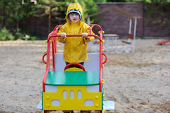 Girl in yellow raincoat on playground Stock Photo
