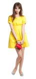 Girl in yellow with red purse. Shy teenage girl in yellow with small vivid red purse Stock Photo