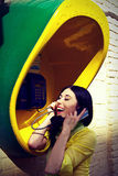 Girl in a yellow shirt in a call-box Stock Images