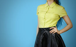 The girl in the yellow shirt and leather skirt. Isolated on blue. Background Royalty Free Stock Photos