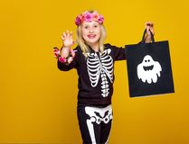 Girl on yellow showing shopping halloween bag and frightening. Colorful halloween. smiling girl in halloween skeleton costume on yellow background showing stock image