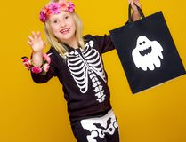 Girl on yellow showing shopping halloween bag and frightening. Colorful halloween. smiling girl in halloween skeleton costume on yellow background showing royalty free stock photography