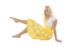 Girl in yellow sitting leg up Stock Image