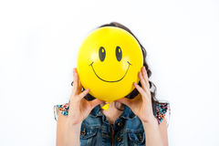 Girl with yellow smiling balloon Royalty Free Stock Images