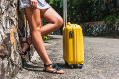 Girl with a yellow suitcase on a resort Royalty Free Stock Images