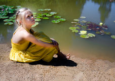 Girl in yellow sundress sitting by the pond with water lilies Stock Images