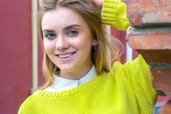 Girl in yellow sweater near red brick wall Stock Image