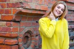 Girl in yellow sweater near red brick wall Stock Photo