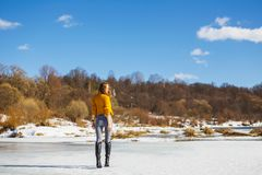 A girl in a yellow sweater with a short haircut stands back on the ice of the river royalty free stock images