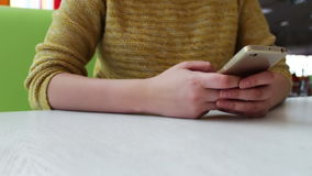 Girl in a yellow sweater is sitting in a cafe and something is typing on a smartphone stock video footage
