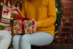 The girl in a yellow sweater unwraps a Christmas gift royalty free stock photo