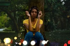 Girl in Yellow Top Sitting Beside Tree royalty free stock photos