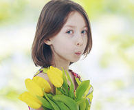 Girl with yellow tulips Stock Photos