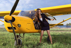 Girl and yellow ultralight aircraft. Ultralight airplane yellow and brunette on a green field Stock Photo