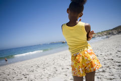 Girl (9-11) in yellow vest and shorts standing on beach, looking at sea, rear view (tilt) Royalty Free Stock Photo