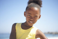 Girl (8-10) in yellow vest standing on beach, smiling, close-up, portrait Royalty Free Stock Photography