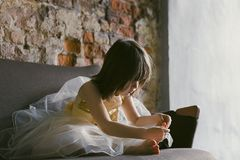 Girl in Yellow-and-white Dress Sitting on Couch While Holding Her Foot royalty free stock photography
