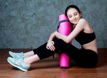 Girl with a yoga mat Royalty Free Stock Photography