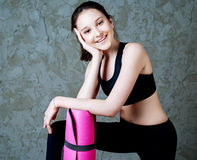 Girl with a yoga mat Royalty Free Stock Photo