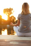 Girl in yoga pose - back view. Body part of girl in yoga pose near water at sunset - back view Stock Image