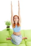 Girl in yoga pose with hands up. Happy red hair girl in yoga pose with hands up in bed at home Stock Photos