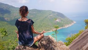Girl in yoga pose with picturesque view of the island at a height. Viewpoint Stock Images