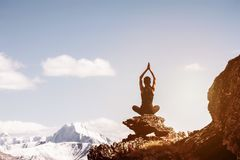 Girl yoga pose sits rock mountains. Girl sits in yoga pose on big rock against snowcapped mountains. Yoga concept with place for text Stock Photography