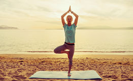 Girl in yoga pose of tree on beach Stock Images