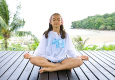 Girl in yoga position by the beach. Stock Photo