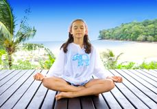 Girl in yoga position by the beach. Royalty Free Stock Image