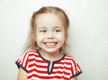 Girl of young age with hazel eyes and smile. Girl of young age with hazel eyes and blonde hair, and smile on face, cheerful child wearing bright and colorful stock images