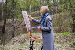 The girl young artist paints a picture in oil on the plein Air . Royalty Free Stock Image
