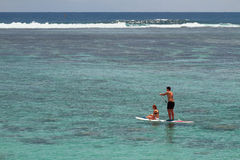 Girl and young man riding board with an oar. Lagoon Hermitage, Reunion. La Reunion Island is a small French island in the South Indian Ocean, 21-01-2016 Royalty Free Stock Photos