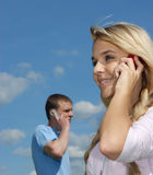Girl and young man speak by a mobile phone. Young beautiful people talk on a cellular telephone against the dark blue sky to clouds Royalty Free Stock Images