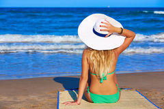 Girl young sitting looking at the sea with beach hat Stock Image