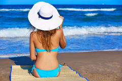 Girl young sitting looking at the sea with beach hat Stock Photography