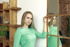 Girl young slim beautiful near the mirror Royalty Free Stock Images