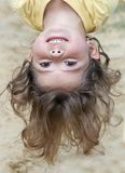 Girl young smile. A picture of a cute young little girl hanging upsidedown stock image
