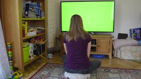 Girl young woman blonde watching chroma key green tv screen sitting stock footage