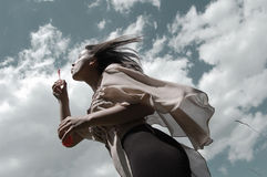 Girl/young woman blowing soap bubbles in the wind. Portrait of a girl/young woman blowing soap bubbles in the wind in the summertime with the  sky and clouds as Stock Image