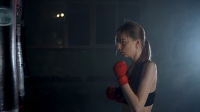 Girl, young woman doing Boxing with a punching bag, kickboxing for self defense stock footage