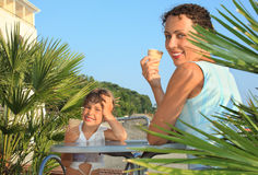 Girl and young woman eat ice-cream near palm trees Stock Photos