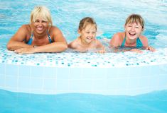 Girl, young woman and middle-aged woman. Girl, young women and middle-aged women in a swimming pool with blue water Stock Photography
