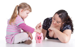 Girl with young woman and piggy bank stock image